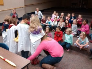 "Chrissy shows the kindergarteners the best way to floss their teeth, using some volunteers from the audience as our ""baby teeth."""